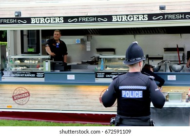 Beaulieu, Hampshire, UK - May 29 2017: Rear view of a British police officer in front of a mobile burger van