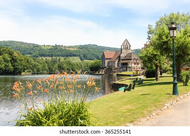 Beaulieu sur Dordogne and the medieval Chapel of the Penitents on the Dordogne River with a weir in the background , Correze, Limousin, France in a picturesque landscape