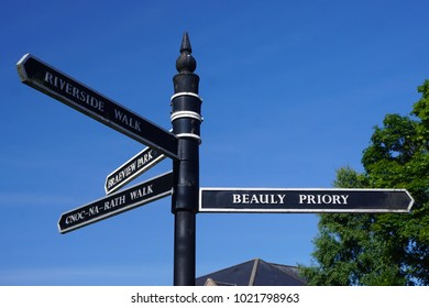 Beauly, County of Inverness, in the Scottish Highlands: Directional signs in English and Scottish Gaelic against a bright blue sky.