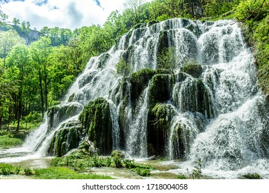 Beaumes-les-Messieurs tuffs waterfall. Rock covered with moss in a natural site. Jura - France. - Shutterstock ID 1718004058