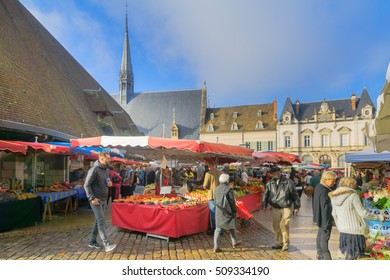 BEAUNE, FRANCE - OCTOBER 15, 2016: Market scene with various product, sellers and shoppers, in Beaune, Burgundy, France