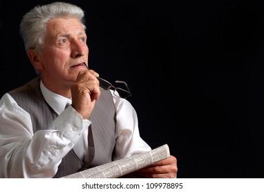 Beauteous elderly man in suit on black background