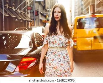Beautful brunette woman walking on New York city street between csrs wearing summer dress at sunny summer day