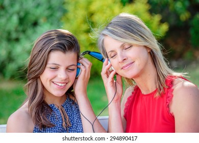 beautful young girl with her mother listening music together with complicity