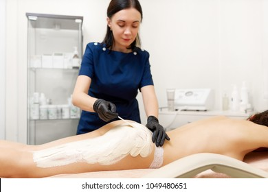 Beautician anointing white clay mask on naked buttocks and legs of client. Woman lying on bed and enjoying procedures, slimming and tighten her body. Concept of beauty industry and skin correction.
