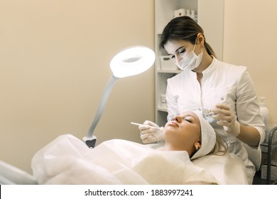 beautician applies cosmetic product to patient woman with brush