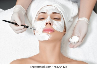 beautician applies the mask to the face of  beautiful young woman in the spa salon. spa treatments