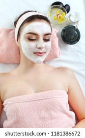 Beautician applying anzymatic peeling on woman's face in spa