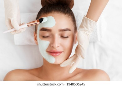 Beautician applying clay face mask on woman face, top view
