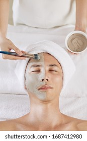 Beautician applying clay mask on face of mature Asian man