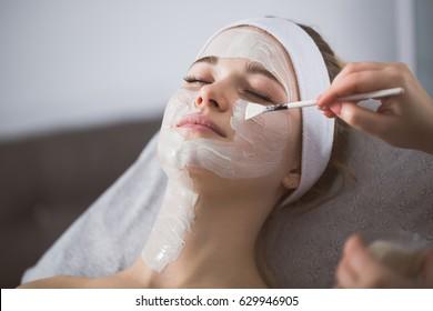 Beautiker, der im Spa auf dem Gesicht der Frau enzymatische Schälung anbringt