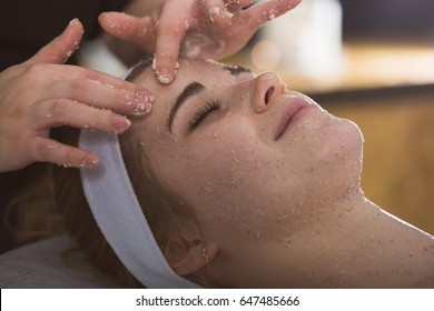 Beautician applying exfoliating salt scrub on woman's face
