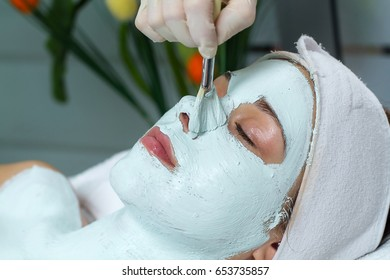 A beautician is applying a face mask on a client's face in the area of her nose. She is doing that with a special brush.