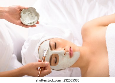 Beautician applying facial mask to the young lady, view from the top