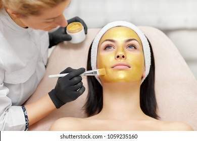 Beautician applying gold mask on client's face with help of brush. Beautiful woman lying and relaxing in beauty salon. Anti wrinkle spa procedures making face moisturize and skin tone even.