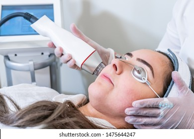 Beautician applying radio frequency microneedling handpiece to a woman's face for skin tightening treatments at a beauty clinic.