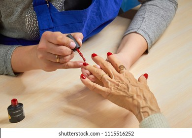 Beautician applying red varnish to woman nails. Manicurist painting nails to elderly woman with red polish on salon table. Old woman receiving manicure.