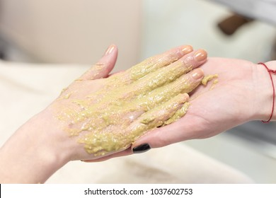 Beautician applying therapeutic mud. Hand treatment with mask in beauty spa salon.