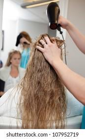 Beautician blow drying woman's hair at parlor