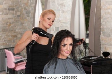 Beautician blow drying woman's hair after giving new haircut at parlor. blond girl drying dark-haired girl hair