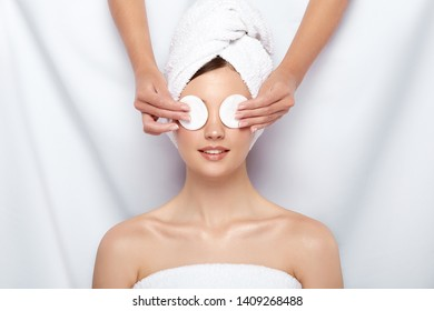 beautician closing woman's eyes with two cotton pads, happy and treated customer of spa procedures, skin care theraphy, relaxation in clinic