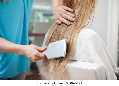 Beautician combing long blond hair of female customer with brush at parlor