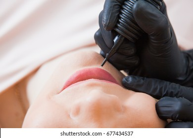 Beautician cosmetologist applying permanent makeup on girl's face. Using tattoo machine. Lip correction in beauty salon closeup