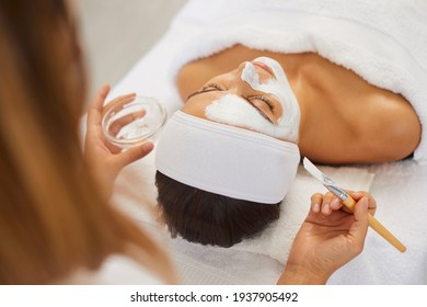 Beautician covering woman facial skin with moisturizing mask during skincare procedure