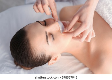 Beautician depilating young woman's face with wax in spa center