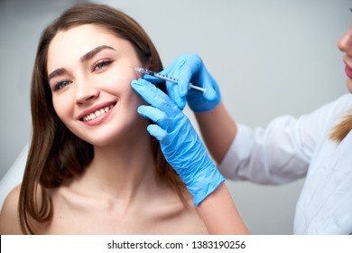 Beautician doctor with botulinum toxin syringe making injection to to remove crow's feet. Cheek volume enhance mesotherapy. Anti-aging treatment and face lift in cosmetology clinic.