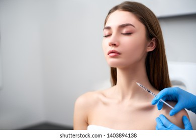 Beautician doctor with botulinum toxin syringe making injection to platysmal bands. Neck rejuvenation mesotherapy. Anti-aging treatment and face lift in cosmetology clinic. Patient lying on chair.