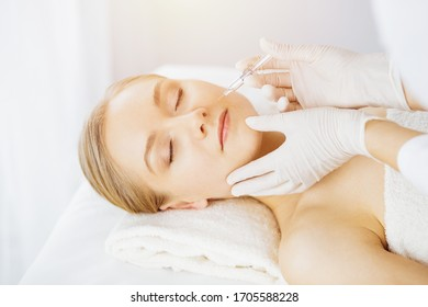 Beautician doctor doing beauty procedure with syringe to caucasian female face in synny room. Cosmetic medicine and surgery, beauty injections concept