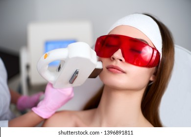 Beautician doctor doing laser RF rejuvenation for pretty young woman face at beauty salon. Elos epilation hair removal procedure. Aesthetic facial acne treatment skin care. Hardware ipl cosmetology