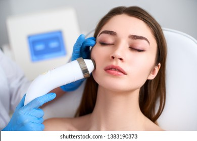 Beautician doctor doing rf-lifting procedure for flawless woman face laying in a beauty salon. Hardware cosmetology. Patient receiving electric facial massage. Skin rejuvenation and wrinkle smoothing.