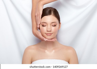 beautician doing facial massage for female customer, pretty fgirl receiving face traetment with open shoulders and in white towel