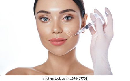 Beautician doing injection into the nasolabial folds. Correction of wrinkles on the female face using dermal fillers
