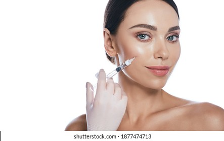 Beautician doing injections dermal fillers into female cheeks for a younger or more beautiful face. Cosmetology, filler treatment