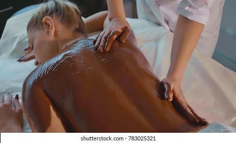 Beautician doing massage with chocolate to young beautiful woman at luxury spa salon. Massage therapist rubs chocolate cream in woman's back and shoulders.