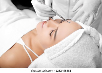Beautician doing mechanical facial cleansing, procedure for cleansing pores and skin from defects