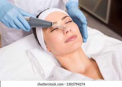 beautician doing physiotherapy whith darsonvalization equipment on woman face at beauty salon
