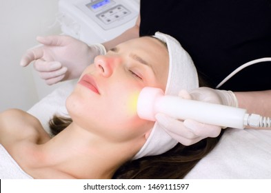 beautician doing red led light therapy to female customer in beauty salon, facial photo therapy for skin pore cleansing. Anti-aging treatments and photo rejuvenation procedure