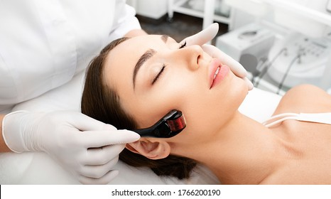 Beautician doing skin treatment using a microneedle derma roller. Woman getting procedure skincare, with mezzo skin roller