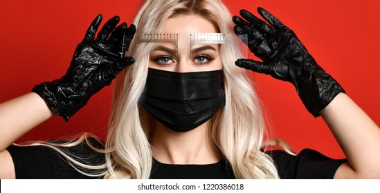 Beautician doing tattooing eyebrow permanent make-up for eyebrows of beautiful woman with thick brows in beauty salon in black gloves and mask on red background