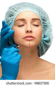 Beautician drawing perforation lines on woman face before plastic surgery operation