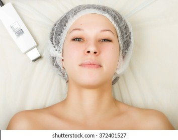 Beautician examining the face of a young female client at spa salon. ultrasonic cleaning person. Professional consultation