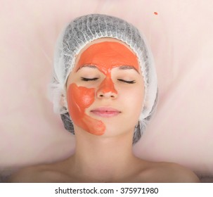 Beautician examining the face of a young female client at spa salon. beautician does cosmetic mask on the patient's face. Professional consultation