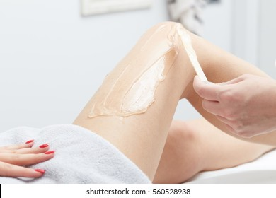 Beautician Giving Epilation wax Treatment To Woman On Thigh