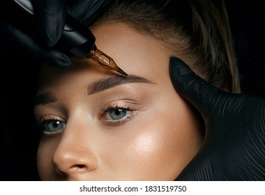 Beautician hand doing brow permanent makeup on an attractive female face