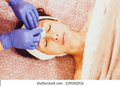 Beautician hands cleaning face of young woman with cotton pad
