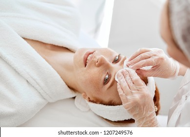 Beautician hands in disposable gloves cleanses with cotton pad female client face, getting ready to the skin care procedure. Woman lies on the couch and looking at camera in beauty clinic.